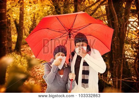 Mature couple blowing their noses under umbrella against tranquil autumn scene in forest