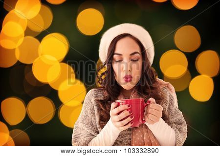 Brunette in winter clothes holding hot drink against blurry yellow christmas light circles