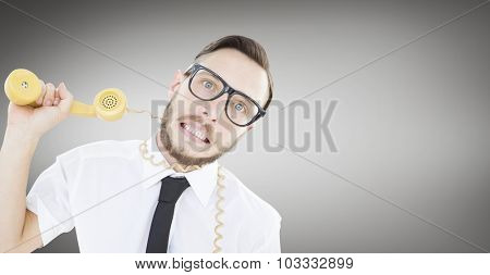 Geeky businessman being strangled by phone cord against grey vignette