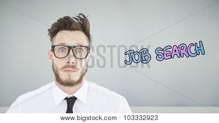 Geeky young businessman looking at camera against room with wooden floor