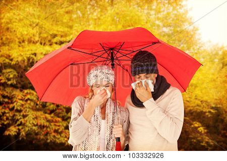 Ill couple sneezing in tissue while standing under umbrella against peaceful autumn scene in forest
