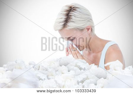 Sick woman blowing her nose against white background with vignette
