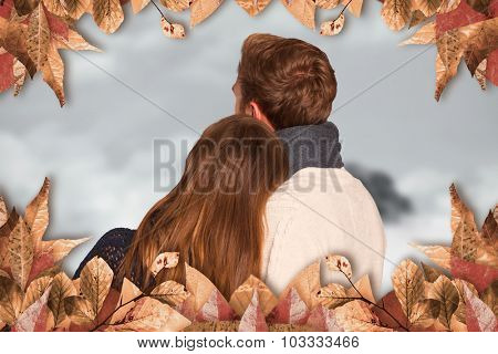 Close up rear view of romantic couple against mountain peak through the clouds