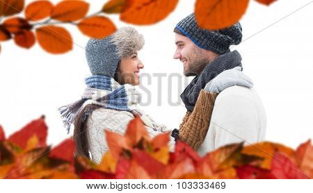 Young winter couple against autumn leaves