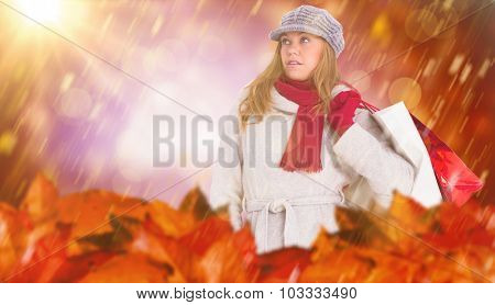 Happy blonde in winter clothes posing against dark abstract light spot design