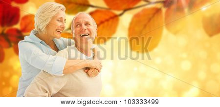 Happy mature couple smiling at each other against autumn scene