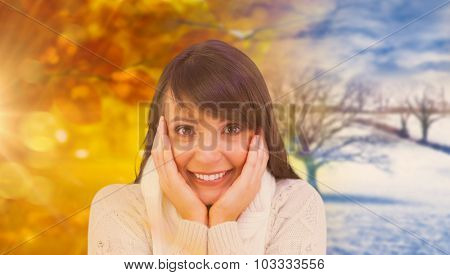 Brunette in winter clothes smiling at camera against autumn turning to winter