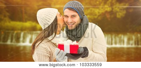 Winter couple holding gift against autumn scene