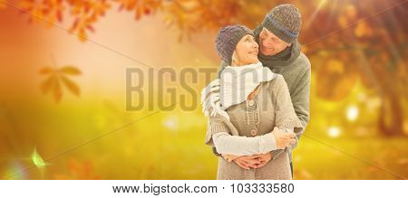 Happy mature couple in winter clothes embracing against autumn scene