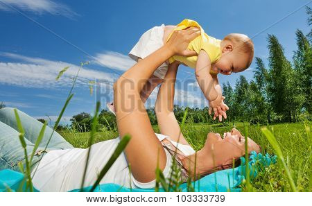 Happy woman lifts her baby up with straight arms