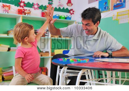 Preschool Teacher And Child Giving High-five
