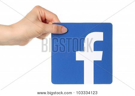 Hand holds facebook logo printed on paper on white background