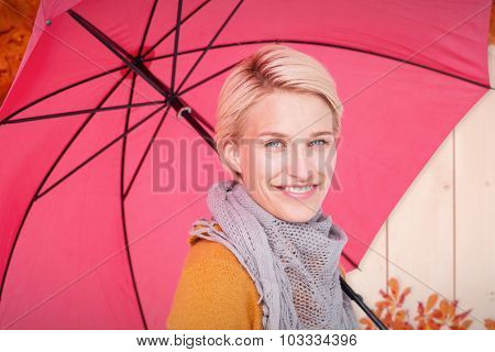 Smiling woman holding an umbrella against autumn leaves pattern