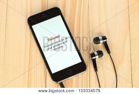 iPhone with Pinterest logotype on its screen and headphones