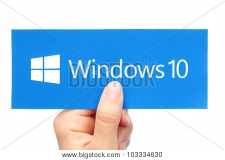 Hand holds Windows 10 logotype printed on paper. Windows 10 is an operating system developed by Micr