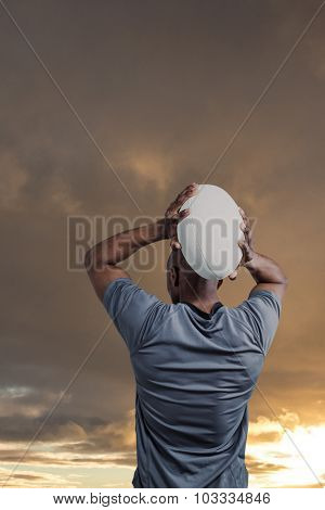 Rear view of sportsman throwing rugby ball against cloudy sky