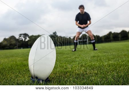 Rugby player about to kick ball at the park