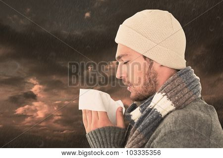 Handsome man in winter fashion blowing his nose against blue and orange sky with clouds