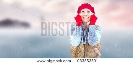 Blonde in winter clothes smiling against calm sea with lighthouse