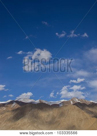 Brown  Mountains And 80 Percent Of Area Of Blue Sky And Some Clouds