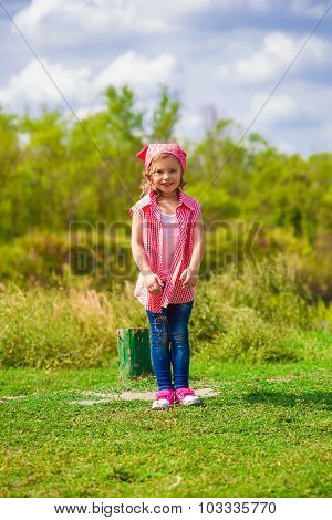 Little girl in jeans and a shirt near a river