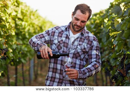 Winemaker In Vineyard With A Glass Of Red Wine And Bottle