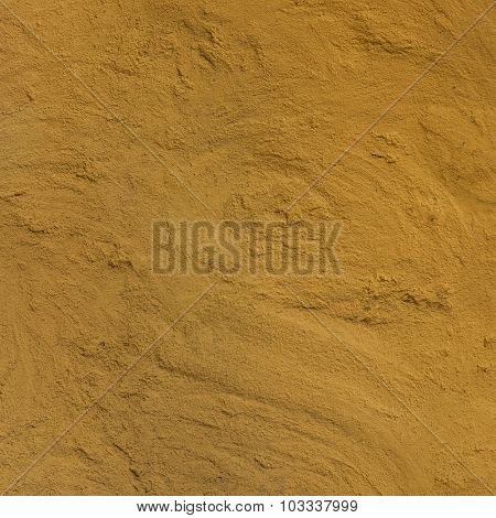 Rough sand plastered wall texture in yellow color.