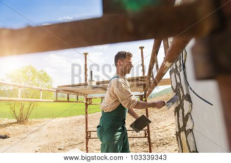 Man putting natural stones on a wall