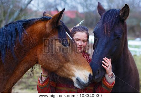 Portrait woman and horses in outdoor. Woman hugging a horse and has feather in her hair