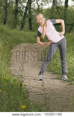 Beautiful Young Blonde Woman Warming Up On A Forest Footpath
