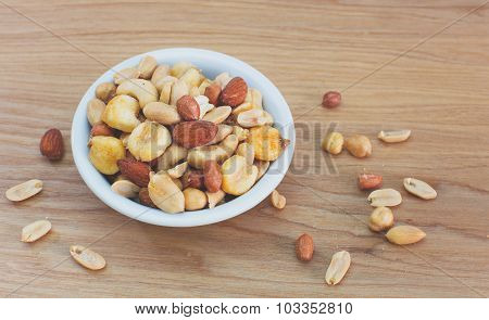 Mixed nuts in small bowl on wood table