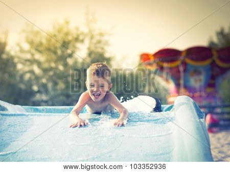 Child On Water Slide At Aquapark, Summer Holiday