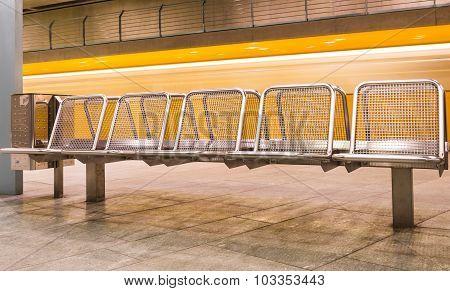 Yellow Train Speeding In Subway Underground Behind Metal Waiting Benches
