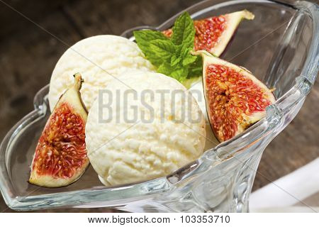 Three scoops of vanilla ice cream with fresh figs in glass bowl, tilted view