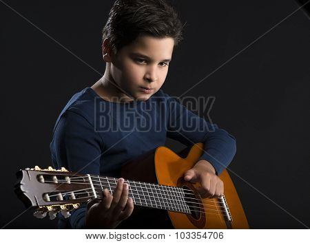 Child guitarist with classical guitar over black background.