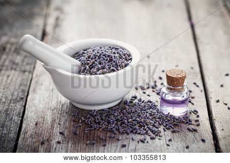 Dry Lavender Flowers In Mortar And Bottle Of Essential Oil On Wooden Table. Selective Focus. Retro S