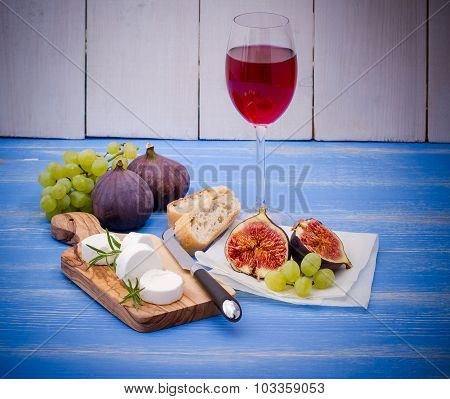 Feta Cheese With Ripe Figs And Wine On Blue
