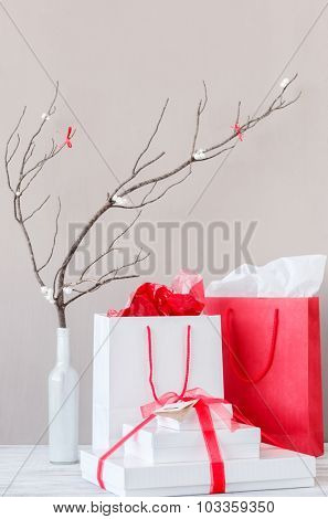 Shopping bags and present gift boxes on table top with elegant interior decoration