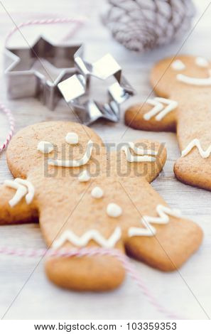 Gingerbread man christmas cookies with festive star shape cutters and holiday pine cone, intentional selective focus on smile