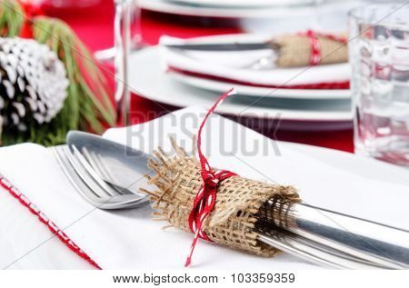Festive holiday dinner setting, white napkins, crockery, cutlery tied with hessian ribbon detail