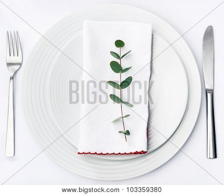 Minimalist dinner place setting, green twig on white napkin on plain crockery and silverware