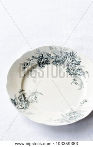 Vintage antique floral plate on white table cloth, plenty of copy space