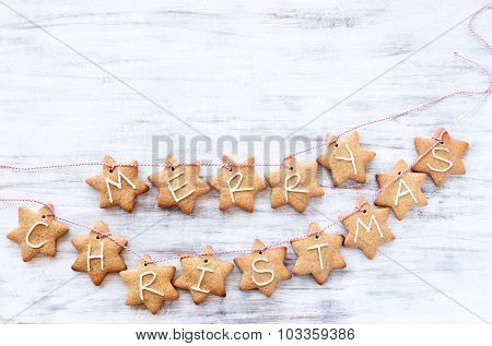 Gingerbread stars with 'merry christmas' tied with bakers twine, white rustic background