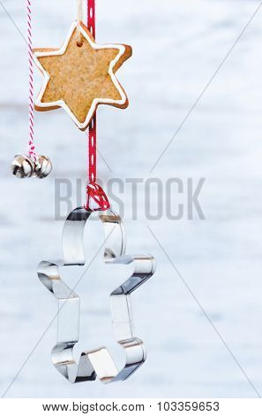 Christmas background with spiced star biscuits suspended with gingerbread man cookie cutter and bells, rustic xmas decoration