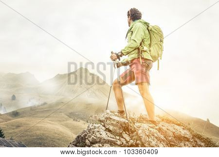 Hiker Climbing On The Mountains. He Stays On The Top Of A Rock And Watch His Goal