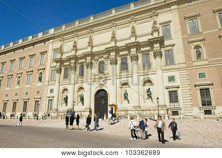 Tourists walk in front of the Royal palace building in Stockholm, Sweden.