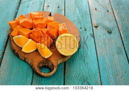 Sweet Butternut Squash, Orange And Lemon Cut On Wooden Board On Turquoise Table