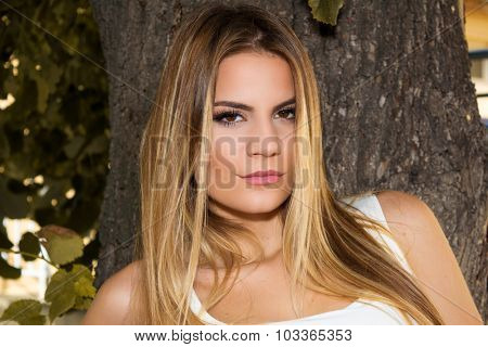 Close-up shot of a beautiful young girl leaning on a tree