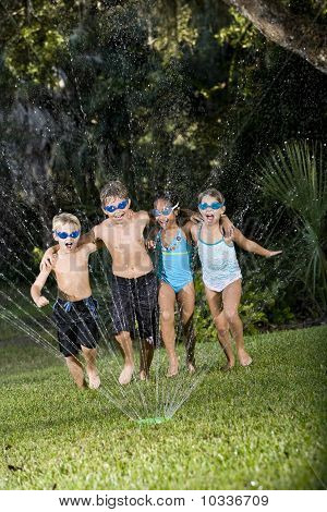 Children Running Through Lawn Sprinkler Together