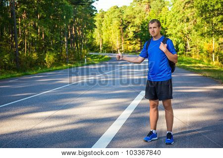 Young Man Hitchhiking On Forest Road